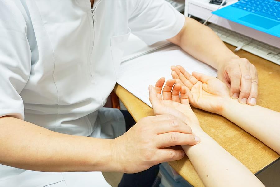 触診する院長と患者さんの手